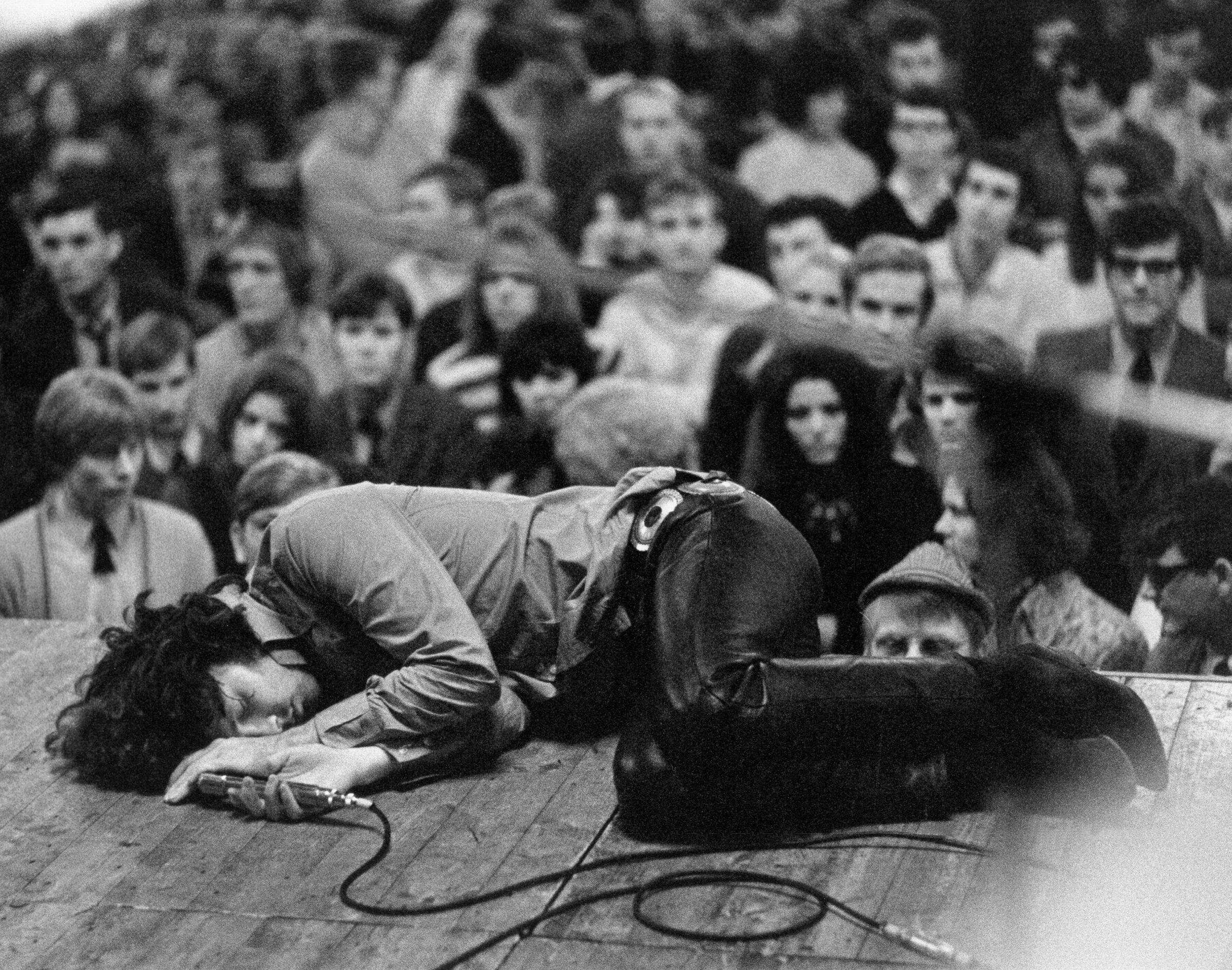 Jim Morrison laying on stage during a performance of The Doors ...