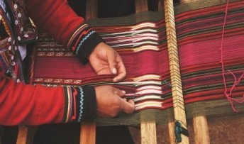 A Native American making clothing on a loom