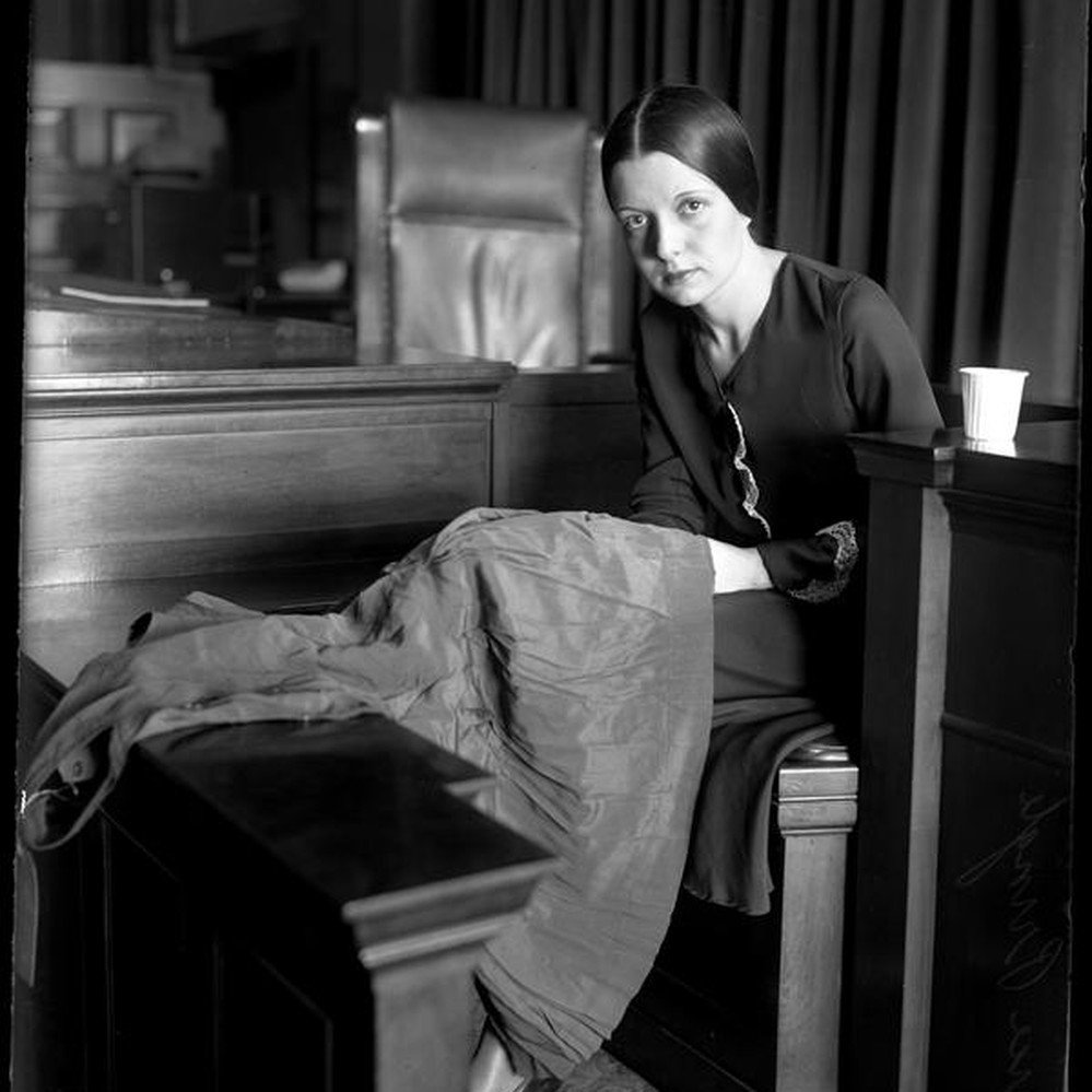 Eunice Pringle on the witness stand examining a dress during Alexander Pantages rape trial — Calisphere